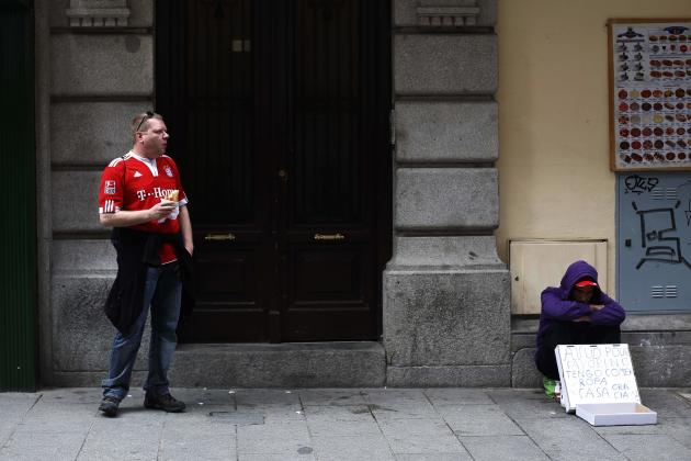 A Bayern Munich supporter eats a sandwich on the street next to a man asking for money in central Madrid
