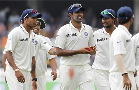 India's Ravichandran Ashwin (C) leaves the field with teammates after dismissing New Zealand's Chris Martin and forcing a follow-on during the third day of their first test cricket match in Hyderabad,