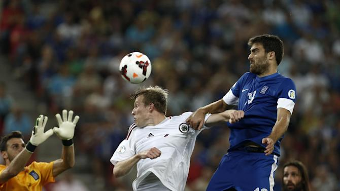 Latvia's Aleksandrs Cauna, center, and  Greece's Sokratis Papastathopoulos challenge for a header as Greece's goalkeeper Orestis Karnezis, left, tries to save the ball during their World Cup Group G qualifying soccer match at the Karaiskaki stadium in Piraeus port, near Athens, on Tuesday, Sept. 10, 2013