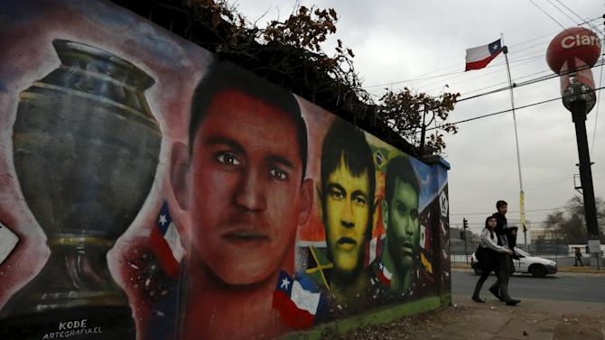 Paintings depicting Chile's Alexis Sanchez, Brazil«s Neymar and Mexico's Rafael Marquez are seen next to at Nacional Stadium in Santiago