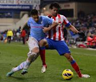 Atletico Madrid's Brazilian forward Diego da Silva Costa (R) vies with Celta's defender Hugo Mallo (L) during the Spanish League football match Atletico de Madrid vs Celta de Vigo at Vicente Calderon stadium in Madrid on December 21, 2012. Atletico Madrid won 1-0