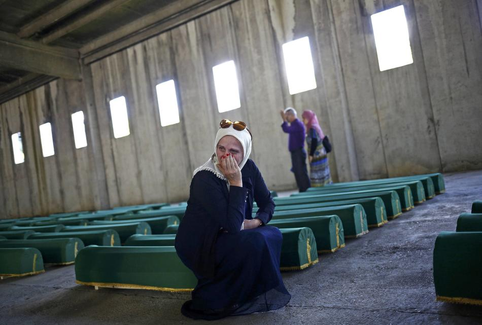 Woman cries near coffins containing the body of newly identified victims of the 1995 Srebrenica massacre at the Memorial Center in Potocari, near Srebrenica