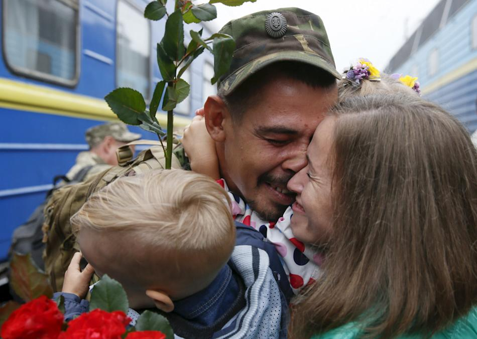 A Ukrainian serviceman embraces his wife and child at a railway station in Kiev after returning from the front line in the Eastern regions of Ukraine