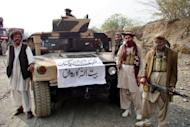 This file photo shows armed militants of Tehreek-e-Taliban Pakistan (TTP), posing for photos next to a captured armored vehicle in the Pakistan-Afghanistan border town of Landikotal, in 2008. Nearly 400 prisoners including militants escaped from a jail in northwestern Pakistan after an attack by insurgents armed with guns, grenades and rockets