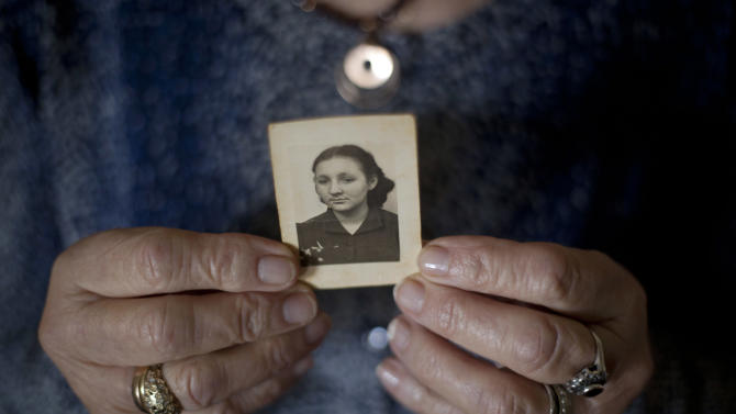 In this Thursday, April 4, 2013 photo, Warsaw ghetto Holocaust survivor Aliza Vitis-Shomron holds a photograph of herself when she was about 17 years old as she sits in her living room in Kibbutz Givat Oz, Israel. Two days before her comrades embarked on an uprising that came to symbolize Jewish resistance against the Nazis in World War II, 14-year-old Aliza Mendel got her orders: Escape from the Warsaw Ghetto. The end was near. Nazi troops had encircled the ghetto, and the remaining Jewish rebels inside were prepared to die fighting. Her job, they told her, was to survive and tell the world about how the fighters died resisting the Nazis. In the 70 years since the revolt, she's been doing just that, publishing a memoir about life in the ghetto and lecturing about the uprising.(AP Photo/Ariel Schalit)
