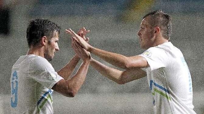 Slovenia's Josip Ilicic, right, celebrates his goal against Cyprus with his teammate Zlatan Ljubijankic during their World Cup group E qualifying soccer match at GSP stadium in Nicosia, Cyprus, Tuesday, Sept. 10, 2013.  Slovenia won the match 2-0