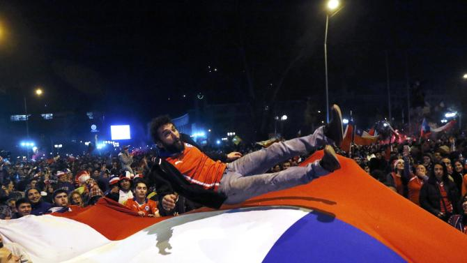 Chilean fans toss a fan on the national flag as they celebrate their team defeating Argentina to win the Copa America 2015 final soccer match at the National Stadium in Santiago