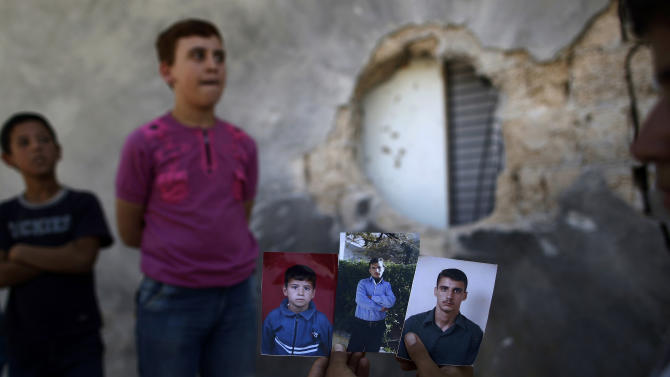 Syrian Hamzah Abu Bakri, Displays portraits of his brothers, from right, Bakri, Mohammed and Abdul Baset, who were killed on Thursday from government forces shelling while standing by their vegetables shop in Tal Rifat, on the outskirts of Aleppo, Syria, Sunday, Sept. 2, 2012. (AP Photo/Muhammed Muheisen)