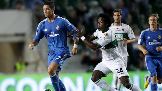 Real Madrid's Cristiano Ronaldo from Portugal drives the ball followed by Elche's  Carlos Alberto Sanchez Moreno  during their La Liga soccer match at the Martinez Valero stadium in Elche, Spain, Wednesday, Sept. 25, 2013