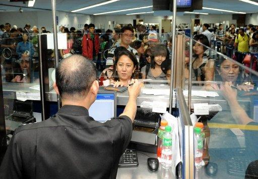 This file photo, taken in 2011, shows a member of the Manila international airport immigration team checking travellers' documents. Philippine airport immigration officials have tightened monitoring of arrivals from Africa after a spate of arrests of drug mules from the continent, according to a spokeswoman