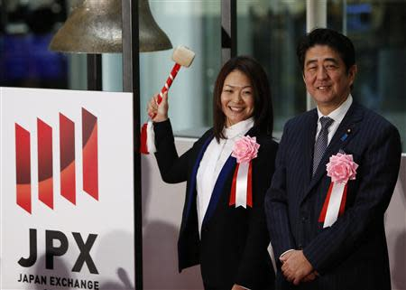 Japan's PM Abe and Japanese Paralympic Sato pose before she rings a bell during a ceremony marking the end of trading in 2013 at the Tokyo Stock Exchange