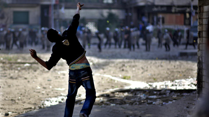 Egyptian protesters clash with security forces near Tahrir square, in Cairo, Egypt, Wednesday, Nov. 28, 2012. Egyptian state television says the country's highest appeal court has decided to suspend its work nationwide to protest the president's decrees giving himself nearly absolute powers.(AP Photo/Khalil Hamra)