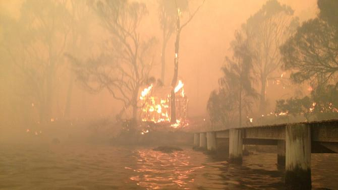 In this Jan. 4, 2013, photo provided by the Holmes family, a building burns near a jetty where Tim and Tammy Holmes attempt to shelter their five grandchildren as a wildfire rages nearby in the Tasmanian town of Dunalley, east of the state capital of Hobart, Australia. The family credits God with their survival from the fire that destroyed around 90 homes in Dunalley. Record temperatures across southern Australia cooled Wednesday, Jan. 9, 2013, reducing the danger from scores of raging wildfires but likely bringing only a brief reprieve from the summer's extreme heat and fire risk.  (AP Photo/Holmes Family, Tim Holmes) EDITORIAL USE ONLY