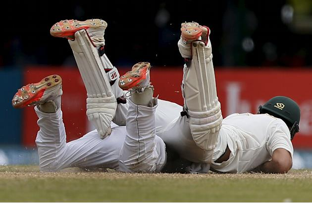 Pakistan's Shehzad collides with Sri Lanka's Silva as he tries to run back to the wicket during the third day of their second test cricket match in Colombo