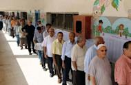 Egyptians queue outside a polling station in Cairo