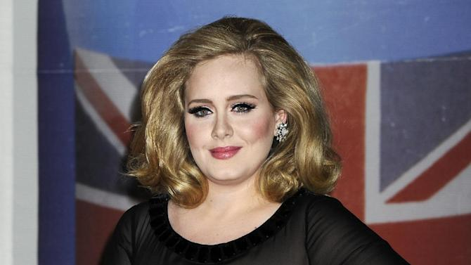 """FILE - In this Feb. 21, 2012 file photo, performer Adele arrives for the Brit Awards 2012 at the O2 Arena in London.  Adele will perform the James Bond theme """"Skyfall"""" at the Oscars, her first U.S. performance since last year's Grammy Awards. The Academy of Motion Picture Arts and Sciences said Wednesday, Jan. 23, 2013, that Adele will sing the Oscar-nominated song at the 85th annual Academy Awards on Feb. 24. She and producer Paul Epworth are nominated for best original song for """"Skyfall.""""  (AP Photo/Jonathan Short, File)"""