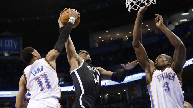 Oklahoma City Thunder guard Jeremy Lamb (11) blocks a shot by Brooklyn Nets forward Paul Pierce (34) as Pierce shoots between Lamb and forward Serge Ibaka (9) in the second quarter of an NBA basketball game in Oklahoma City, Thursday, Jan. 2, 2014. (AP Photo/Sue Ogrocki)