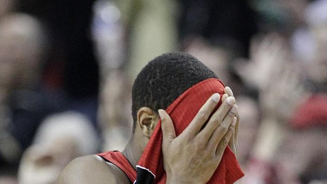 Toronto Raptors guard DeMar DeRozan covers his face as he walks off the court after losing an NBA basketball game against the Portland Trail Blazers in Portland, Ore., Saturday, Feb. 1, 2014.  DeRozan scored 36 points as the Trail Blazers won 106-103