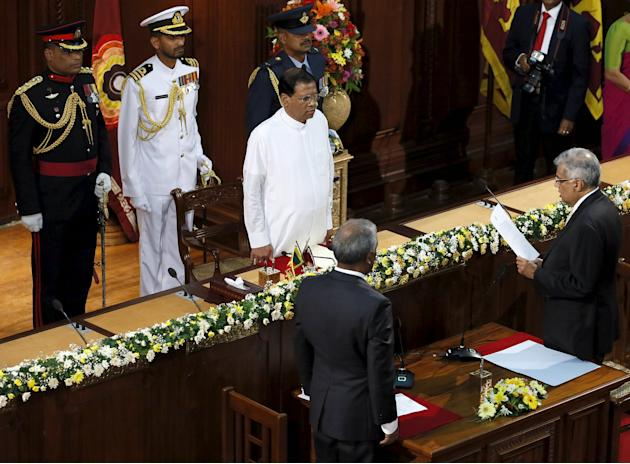 Sri Lanka's Prime Minister Wickremesinghe takes an oath as he is sworn in as minister of policy planning and economic affairs in front of Sri Lanka's President Sirisena during the swearing in