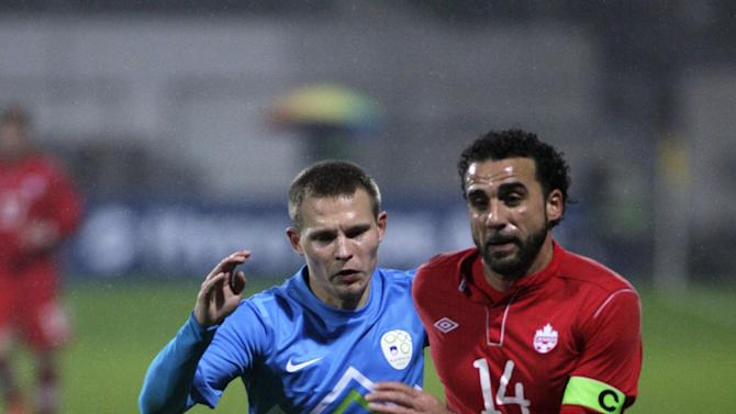Slovenia's Dalibor Stevanovic left, is challenged by Canada's Dwayne De Rosario during a friendly soccer match between Slovenia and Canada, in Celje, Slovenia, Tuesday, Nov. 19, 2013