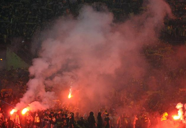 Malaysian supporters light flares after the AFF Suzuki Cup 2014 football match between Malaysia and Vietnam at the Shah Alam Stadium in Shah Alam on the outskirts of Kuala Lumpur on December 7, 2014