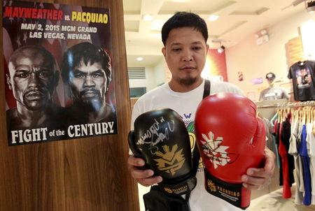 Fan looks at boxing gloves signed by boxer Manny Pacquiao of the Philippines, on sale at a mall in Manila