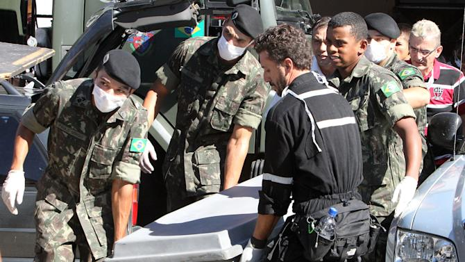 Brazil's soldiers carry a container with the remains of a victim outside a gymnasium where bodies were brought for identification in Santa Maria city, Rio Grande do Sul state, Brazil, Sunday, Jan. 27, 2013. Flames raced through a crowded nightclub in southern Brazil early Sunday, killing more than 230 people as panicked partygoers gasped for breath in the smoke-filled air, stampeding toward a single exit partially blocked by those already dead. (AP Photo/Nabor Goulart)