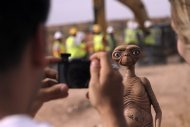 A man takes a photo of an E.T. doll in Alamogordo, N.M, Saturday, April 26, 2014. Producers of a documentary dug in an southeastern New Mexico landfill in search of millions of cartridges of the Atari 'E.T. the Extra-Terrestrial' game that has been called the worst game in the history of video gaming and were buried there in 1983. (AP Photo/Juan Carlos Llorca)
