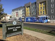"""In this Sept. 17, 2016 photo, a sign identifying Sonny Lawson Park sits while a commuter rail passes in Denver's Five Points neighborhood. The historic black neighborhood was once called """"The Harlem of West,"""" a place where Billie Holiday, Count Basie and Miles Davis performed and novelist Jack Kerouac tried to capture the spirit of the bebop movement in """"On The Road."""" (AP Photo/Russell Contreras)"""