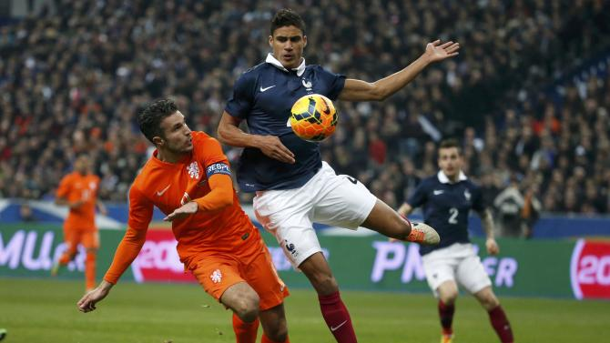 Netherlands' Van Persie challenges France's Varane during their international friendly soccer match at the Stade de France in Saint-Denis