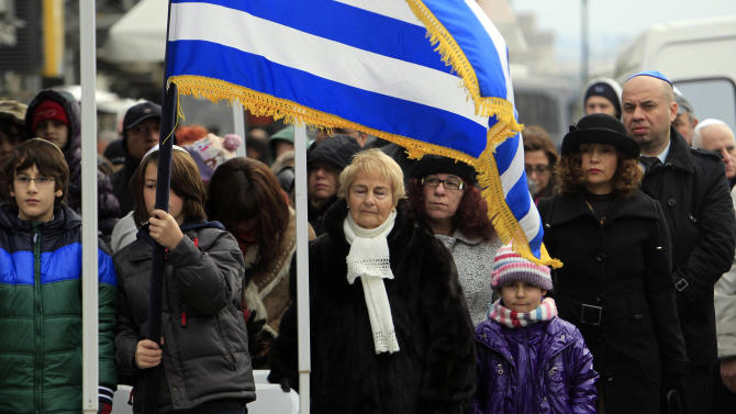 People attend a  ceremony at the Holocaust Memorial commemorating the persecution of the Jewish people during World War II, in Thessaloniki, northern Greece, on Sunday, Jan. 27, 2013. There were around 50,000 Jews living in Thessaloniki at the start of World War II, and almost 45,000 perished at Auschwitz concentration camp, and Greece officially commemorates the Holocaust every Jan. 27. (AP Photo/Nikolas Giakoumidis)