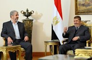 Egyptian President Mohamed Morsi (R) meets with Hamas leader Khaled Meshaal in Cairo on January 9, 2013. Palestinian president Mahmud Abbas and Meshaal have agreed to expedite a stalled reconciliation deal between the rival factions, a Hamas official said Thursday