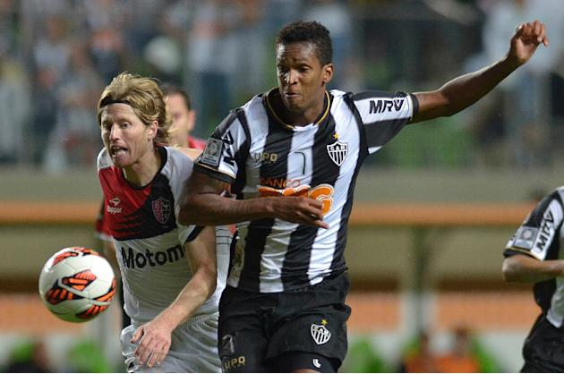 Milton Casco (left), of Argentina's Newell's Old Boys, vies for the ball with Jo, of Brazil's Atletico Mineiro, during their 2013 Copa Libertadores second leg semifinal football match at A