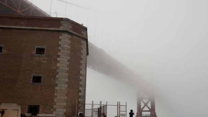 "In this photo taken Thursday, Sept. 27, 2012, a man stands beside Fort Point and looks out at the fog-covered Golden Gate Bridge in San Francisco. San Francisco has a long history as a favorite site for filmmakers and the movie buffs who want to see the spots where their favorite scenes took place, from Fort Point under the Golden Gate Bridge where Jimmy Stewart saved Kim Novak in ""Vertigo"" to the steps of City Hall, where Sean Penn gave an impassioned speech in ""Milk,"" to Alcatraz, stage for Clint Eastwood and many others. (AP Photo/Eric Risberg)"