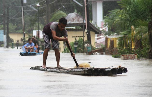 Residents ride on makeshift rafts along a flooded road after tropical storm Linfa hit Luna, La Union