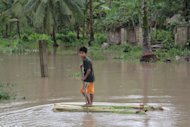This file photo shows a boy riding on a makeshift raft as he makes his way near his flooded home in southern Philippines, on December 4, 2012. The death toll from a tropical storm that hit the central Philippines on Christmas Day has risen to 20, with more than 20,000 others left homeless, according to the government