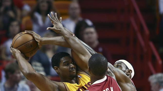Miami Heat players Chris Bosh (1) and LeBron James (6) force Cleveland Cavaliers' Andrew Bynum to pass the ball during the first half of a NBA basketball game in Miami, Saturday, Dec. 14, 2013