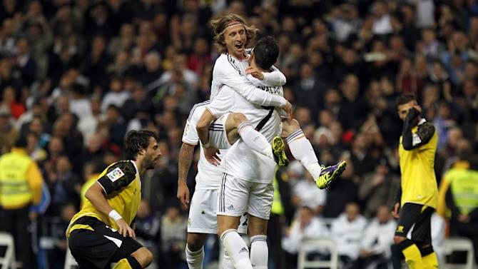 Real Madrid's Cristiano Ronaldo, centre right, from Portugal, celebrates with teammate Luka Modric from Croatia, top, after Ronaldo scored a goal against Sevilla during a Spanish La Liga soccer match between Real Madrid and Sevilla at the Santiago Bernabeu stadium in Madrid, Spain, Wednesday Oct. 30, 2013. Ronaldo scored a hat trick in Real Madrid's 7-3 victory