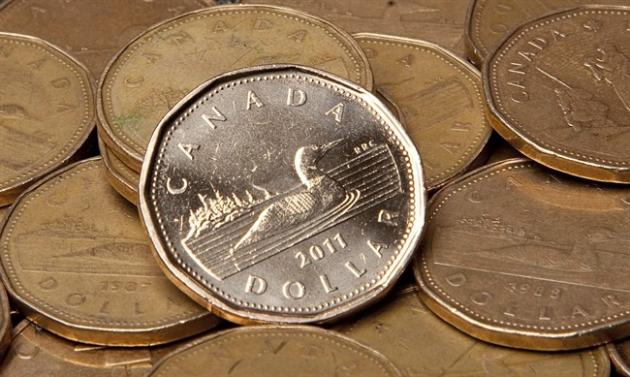 Canadian dollars are pictured in Vancouver, Sept. 22, 2011. The Canadian dollar closed lower Monday amid sliding prices for oil and gold.The loonie declined 0.05 of a cent to 85.99 cents US. THE CANADIAN PRESS/Jonathan Hayward