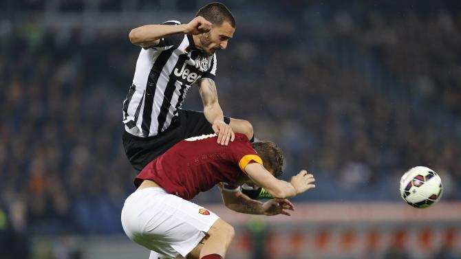 AS Roma's Totti challenges Juventus' Bonucci during their Italian Serie A soccer match at the Olympic stadium in Rome
