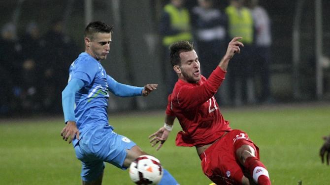 Slovenia's Bostjan Cesar, left, is challenged by Canada's Stefan Cebara during a friendly soccer match between Slovenia and Canada, in Celje, Slovenia, Tuesday, Nov. 19, 2013