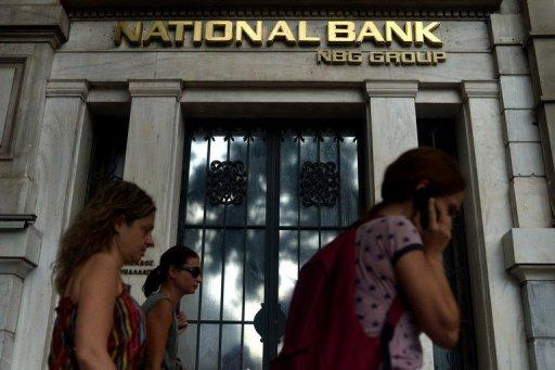 People pass a branch of the National Bank of Greece in Athens. Greece's banking sector is bracing for what local media called a super deal, following the announcement of the National Bank's offer to purchase the third-largest lender Eurobank.