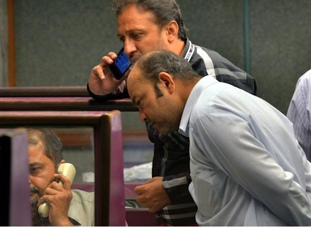 Pakistani stockbrokers talk on their phones as they watch share prices during a trading session at the Karachi Stock Exchange (KSE) in Karachi on September 2, 2015