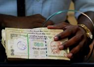 An employee waits to deposit Indian rupee notes at a bank in Mumbai. India's rupee traded mostly down against the dollar on Tuesday, at near record lows, even as the country's central bank was likely to have intervened to prop up the ailing currency, analysts said