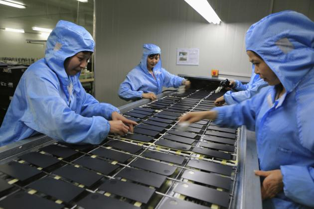 Workers process laptop accessories at a factory in Dazu, Chongqing Municipality