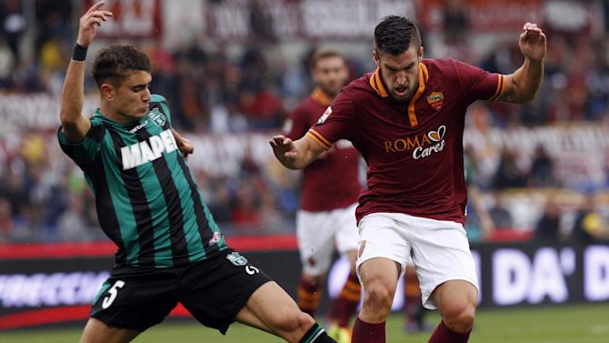 Sassuolo defender Luca Antei, left, and AS Roma midfielder Kevin Strootman, of the Netherlands, fight for the ball during a Serie A soccer match between AS Roma and Sassuolo at Rome's Olympic stadium, Sunday, Nov. 10, 2013
