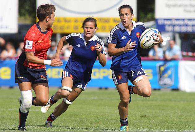 France's Fanny Horta (R) runs with the ball during the Seven's Women Grand prix series final rugby match between France against Spain on June 21, 2015 at the Malemort stadium in Malemort-sur-C