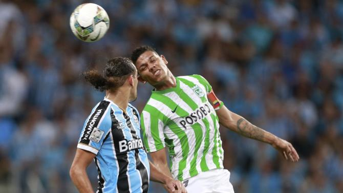 Mejia of Colombia's Atletico Nacional jumps for the ball against Barcos of Brazil's Gremio during their Copa Libertadores match in Porto Alegre
