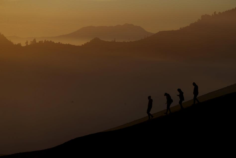 People walk on the slope of Bromo mountain as they attend the Kasada Festival in Probolinggo