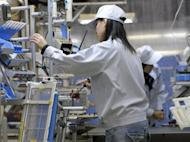 This file photo shows Hitachi workers assembling an air conditioner's automatic filter cleaning system at the Hitachi Appliances Tochigi Works plant in the town of Ohira, Tochigi prefecture, in 2009. Hitachi on Tuesday said it plans to slash its annual costs 5.0 percent by 2015, or about $5.43 billion a year, to compete with rivals including General Electric